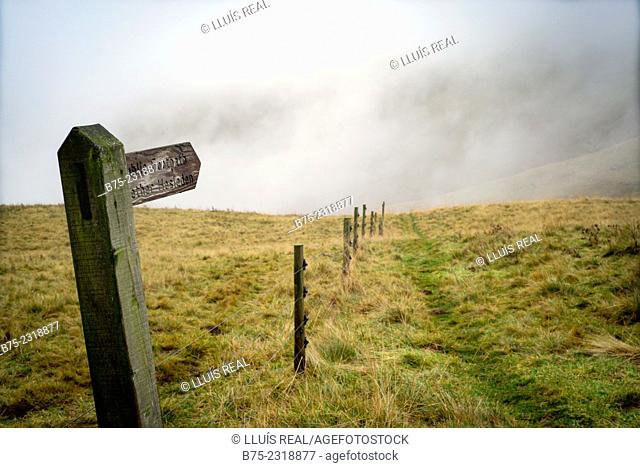Signal of a public footpath to Nether Hesleden in a hill with fog on the background and a fence, Yorkshire Dales, England, UK