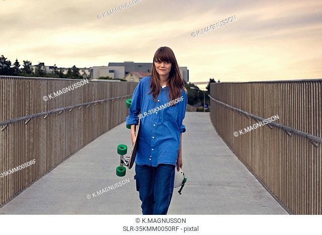 Girl carrying skateboard on walkway