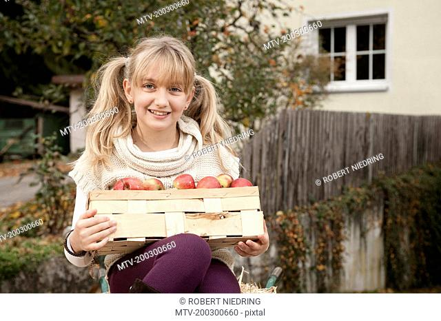 Blond girl holding crate with apples