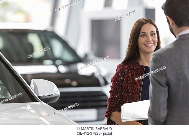 Smiling female customer listening to car salesman in car dealership showroom