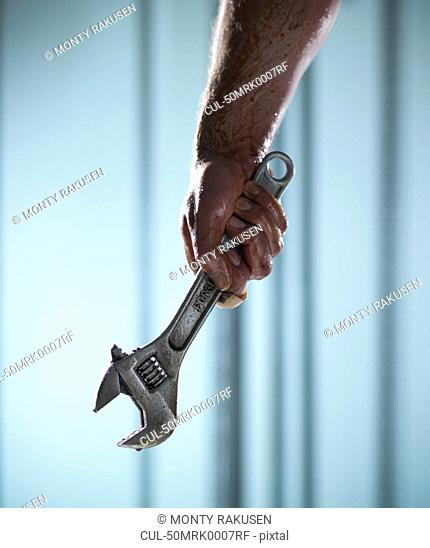 Close up of hand holding wrench