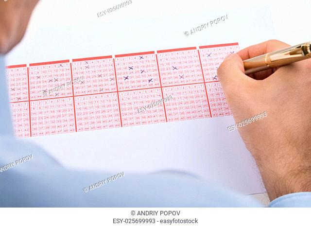Close-up Of Businessperson Marking On Lottery Ticket
