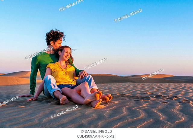 Romantic mid adult couple sitting on sand dunes at sunset, Maspalomas, Gran Canaria, Canary Islands, Spain