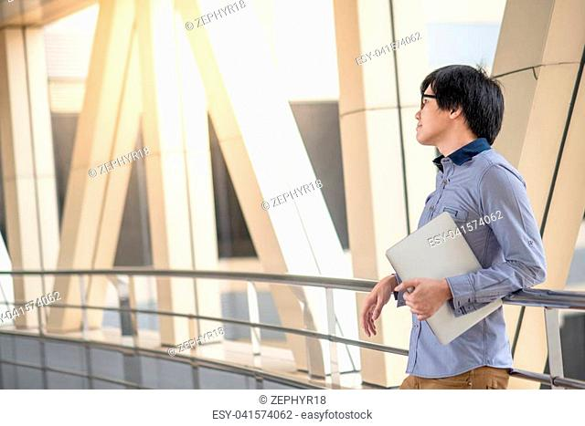 Young Asian man dressed in casual style holding laptop computer in the city, modern IT lifestyle with work life balance concept