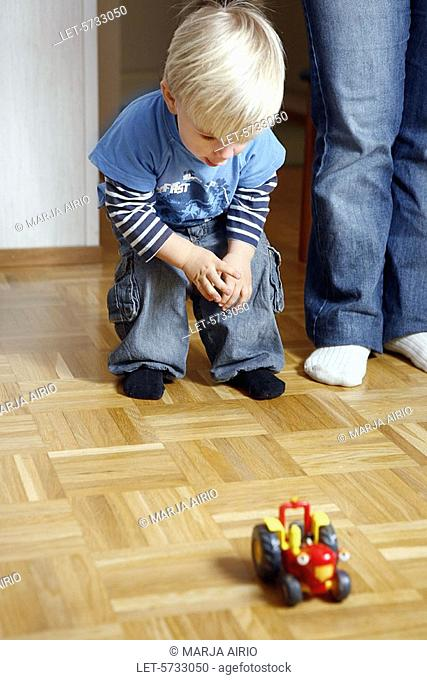 A two-year-old little boy is playing with a toy tractor