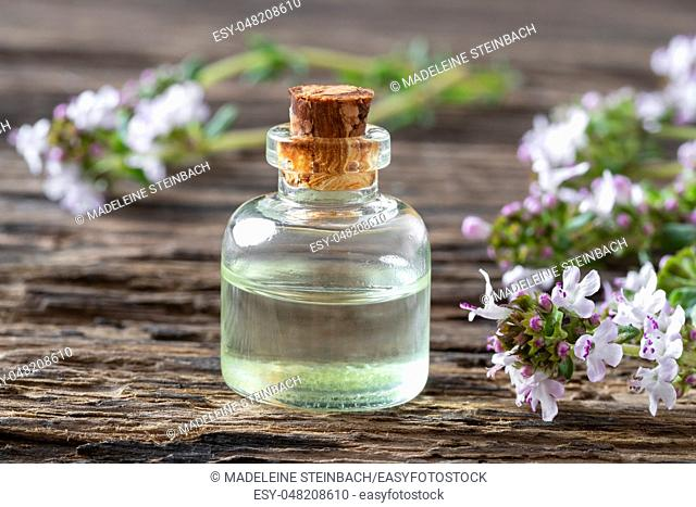 A bottle of essential oil with fresh blooming thyme on a rustic background