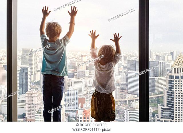 Thailand, Bangkok, boy and little girl looking through window at cityscape