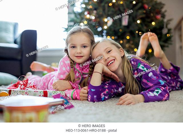 Portrait of girls lying in front of Christmas tree