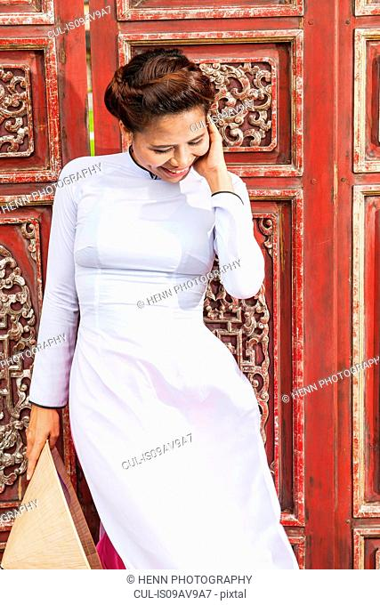 Mid adult woman wearing ao dai dress holding conical hat standing in front of ornate wooden doors looking down smiling, Hue, Vietnam