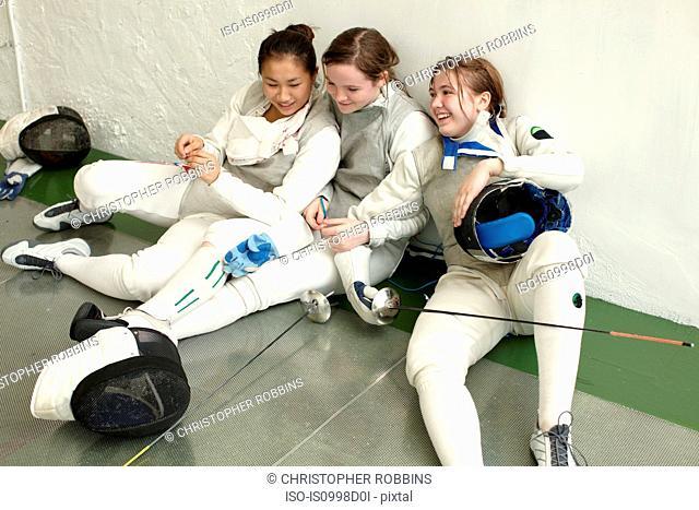 Female fencers sitting together