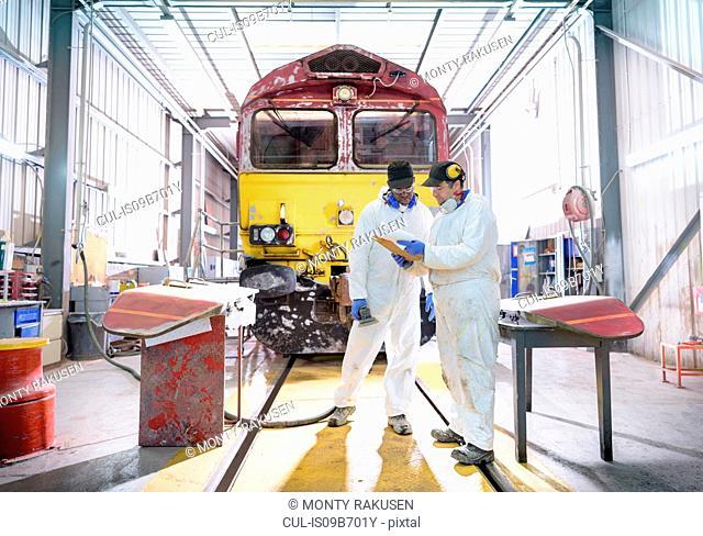 Painters in paintshop with refurbished locomotive in train works