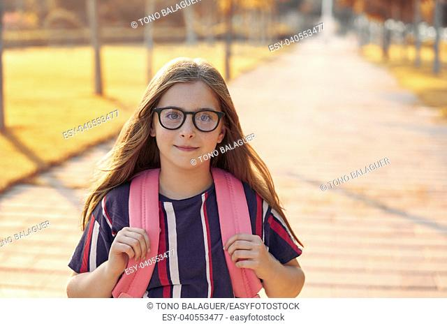 Blond kid student girl with glasses and backpack in the park back to school