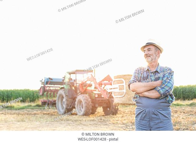Confident farmer in front of tractor on field