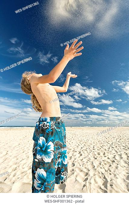 Australia, New South Wales, Pottsville, boy on beach throwing sand in the air