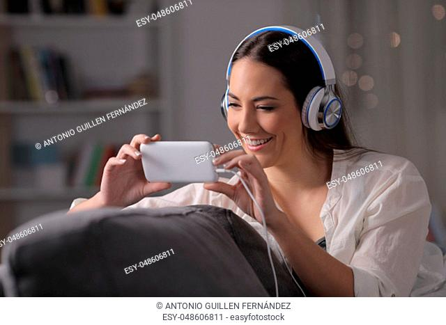 Happy woman watches videos wearing headphones sitting on a couch in the night at home