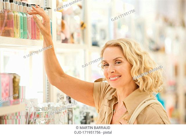 Smiling woman reaching for perfume on store shelf