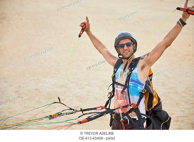 Portrait confident, carefree male paraglider strapped with equipment on beach