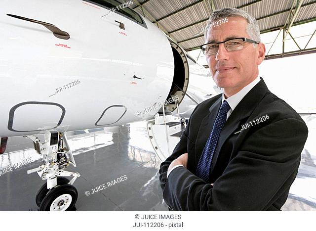 Smiling Businessman standing in front of private jet in hangar