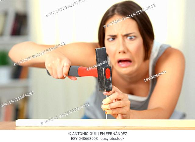 Fronf view of a woman hitting finger with a hammer at home