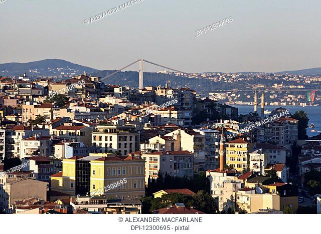 Golden hour light view over Istanbul rooftops towards Bosphurus Bridge between Europe and Asia; Istanbul, Turkey