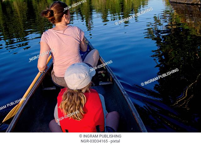 Woman rowing a boat with her daughter, Lake of the Woods, Ontario, Canada