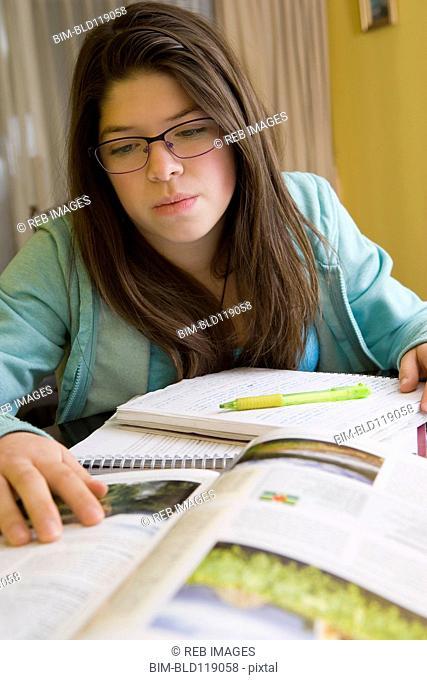 Hispanic girl doing homework at table