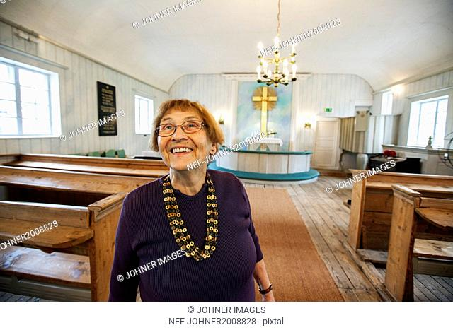Smiling senior woman in church
