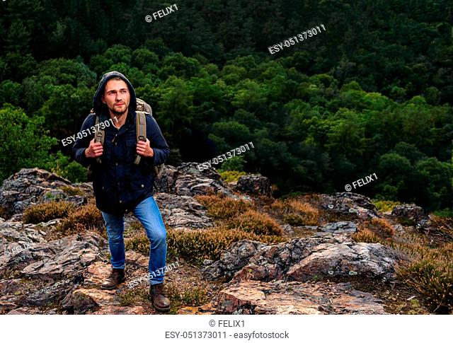 Hipster young man with backpack enjoying mountain. Tourist traveler on background view forest. mock up text. Picos de Europa