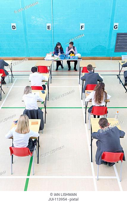 Teachers supervising middle school students taking examination at desks in school gymnasium