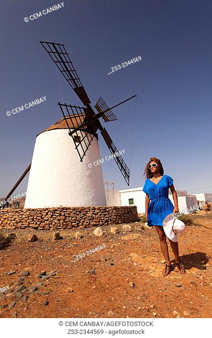 Woman posing in front of the windmill near Antigua, Fuerteventura, Canary Islands, Spain, Europe