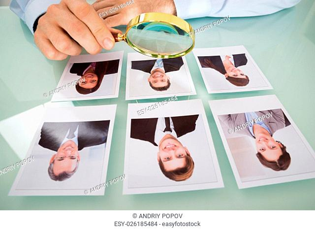 Close-up Of A Person Hand With Candidate Photograph And Magnifying Glass