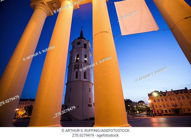 Night view of Vilnius Belfry (Bell Tower) framed through the portico columns of the Cathedral Basilica of St. Stanislaus and St. Ladislaus