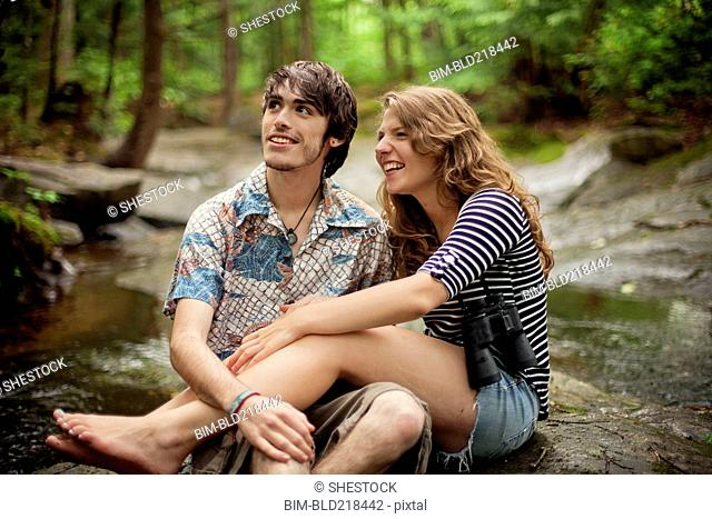 Couple sitting barefoot on boulders in forest
