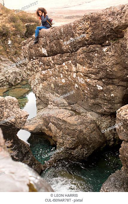 Woman sitting on rocks, Fairy Pools, Isle of Skye, Hebrides, Scotland