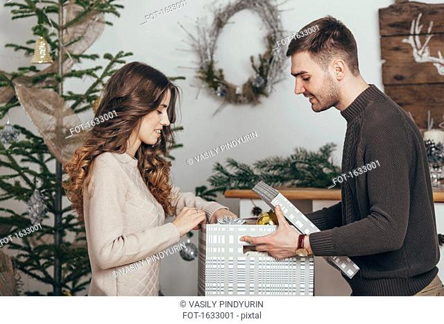 Side view of smiling couple packing Christmas gifts at home