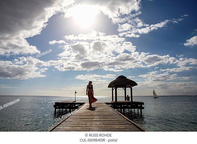 Woman walking along pier, Flic-en-Flac, Mauritius