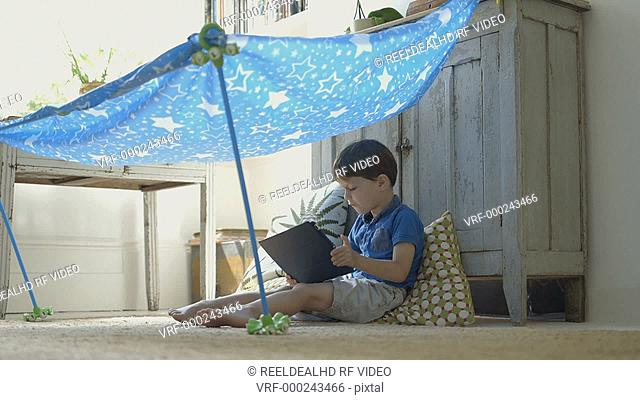 Boy playing with digital tablet under toy tent