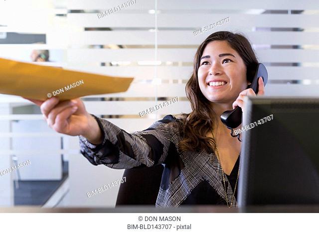 Mixed race businesswoman handing folder in office