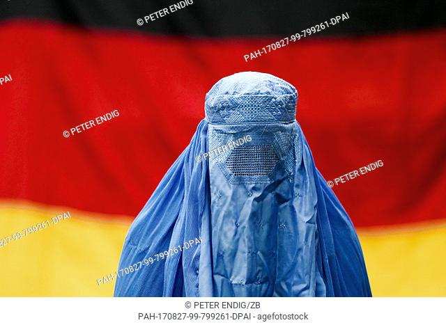 ILLUSTRATION - A woman wearing a burqa in front of a German flag in Leipzig, Germany, 26 August 2017 (posed scene). Photo: Peter Endig/dpa-Zentralbild/ZB