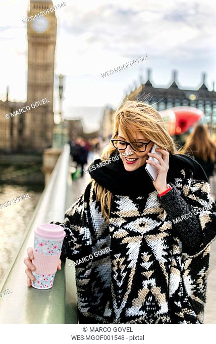 UK, London, young woman talking on phone on Westminster Bridge