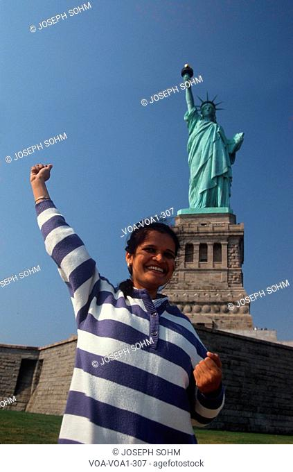 Indian American woman raising arm, Statue of Liberty, New York