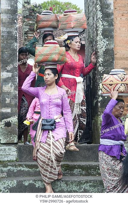 Balinese women carry offerings out through the gate of a Hindu temple in Ubud, the cultural capital of Bali, Indonesia
