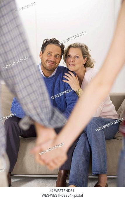 Teenage couple holding hands, parents sitting on sofa