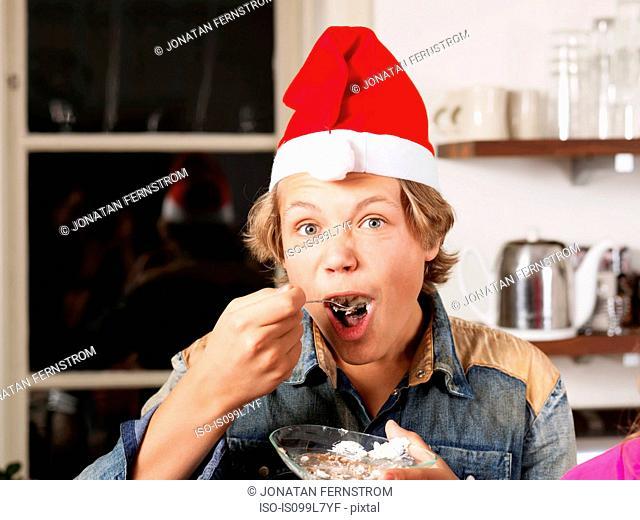 Portrait of teenage boy wearing Santa hat eating cake