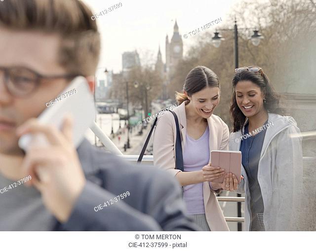 Female friends using digital tablet on urban bridge, London, UK