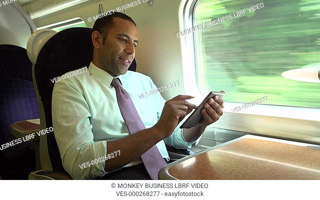 Businessman sitting at table looking at e-reader.Shot on Sony FS700 in PAL format at a frame rate of 25fps