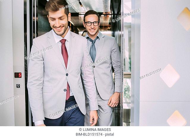 Caucasian businessmen walking out of elevator
