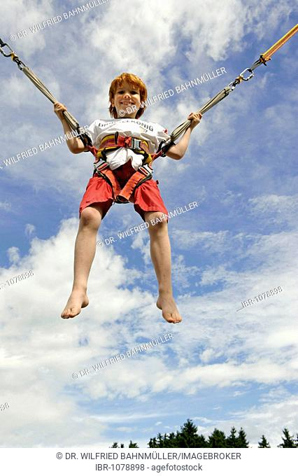 Young boy jumping on a bungee trampoline and flying in the air