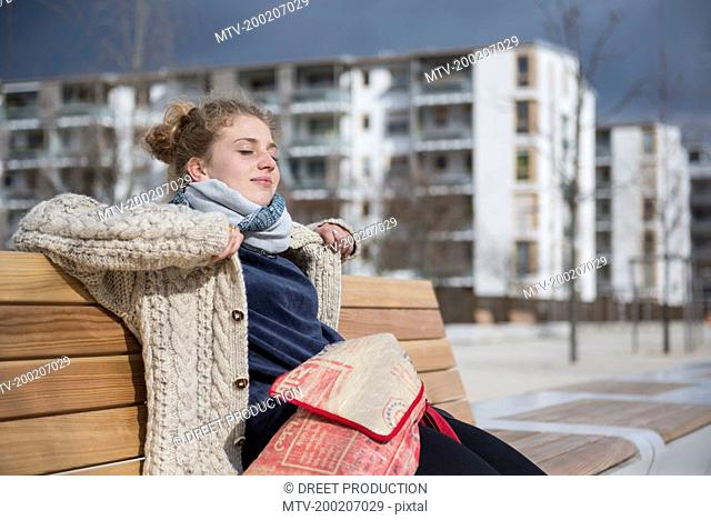 Young woman sitting on bench in city, Munich, Bavaria, Germany
