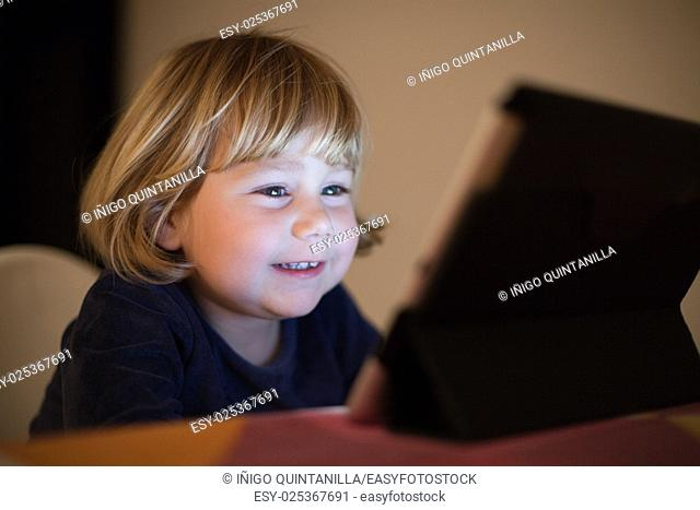 blonde two years old baby blue sweater, sitting inside home at night reading and watching digital tablet, face illuminated by the light of the screen smiling...